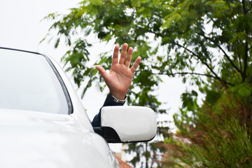 Driver waves from a car window