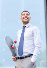 young smiling businessman with skateboard outdoors