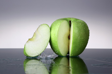 Green apple with slice and water drop