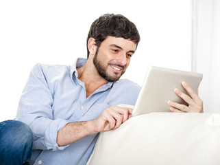 Young attractive Latin man at home using digital tablet pad