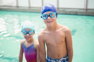 Cute little siblings standing poolside