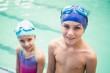 Cute little siblings standing poolside - 72333896