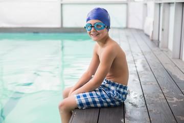 Cute little boy sitting poolside