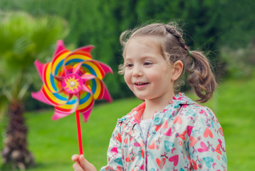 little cute girl playing with pinwheel in nature