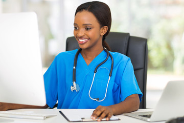 young african female doctor using computer