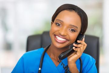 african american female nurse using landline phone