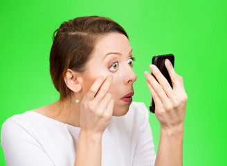 exhausted woman looking in a mirror isolated on green background