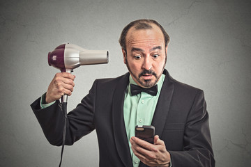 business man reading news on smartphone holding hairdryer