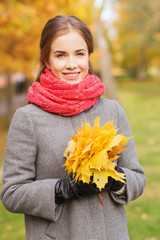 smiling woman with bunch of leaves in autumn park