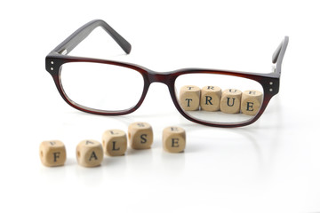 message false blurry and true in sharp letters behind glasses