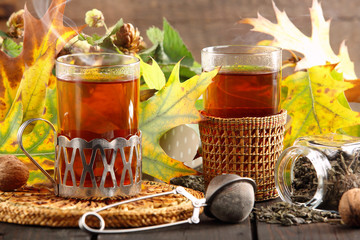 Hot green tea in a glass on a wooden background with autumn leav