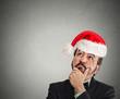 xmas man with red santa claus hat looking up thinking