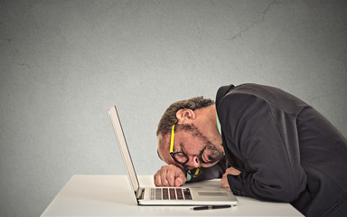 Businessman sleeping on a laptop exhausted long working hours
