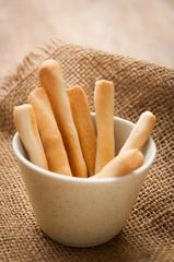 Breadsticks in napkin on wooden background.