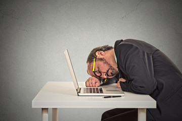 Businessman sleeping on a laptop on grey wall office background