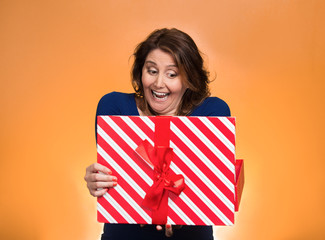 Portrait happy excited middle aged woman opening red gift box