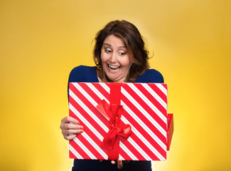 happy excited woman opening red gift box on yellow background
