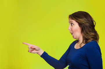 Surprised female pointing out at copy space, green background