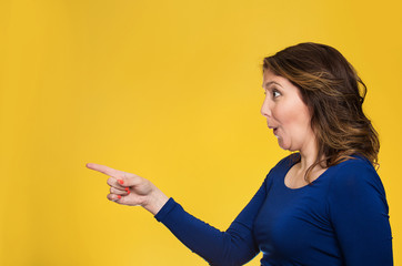 Surprised female pointing out at copy space on yellow background