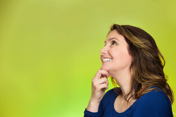 thoughtful happy woman looking up dreaming on green background