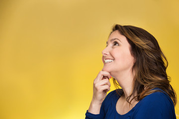 Closeup thoughtful happy woman looking up on yellow background