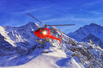 Red helicopter landing at swiss ski resort near Jungfrau mountai