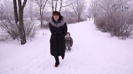 mother rolling a child on a sledge