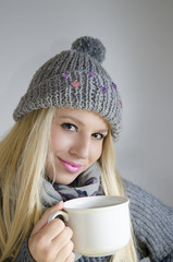 Cute blonde with wool cap and sweater holding cup of tea