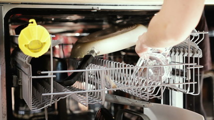 Woman loading dishwasher and closing it