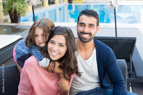 Family close to the pool poster