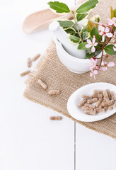 Herbal medicine pills over white background