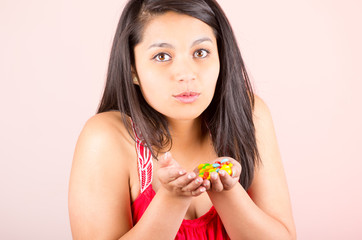 beautiful young hispanic girl holding candy sweets caramel
