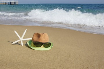 Straw Hat, Sunglasses and  Starfish on the Empty Sea Beach