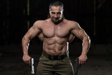 Muscular Man Holding Guns