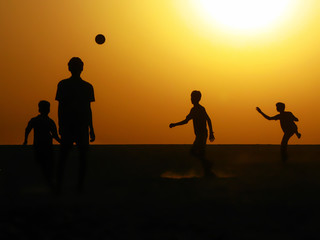 Silhouette of Boys Playing Football at Sunrise