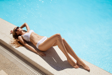 Young woman sunbathing near swimming pool.