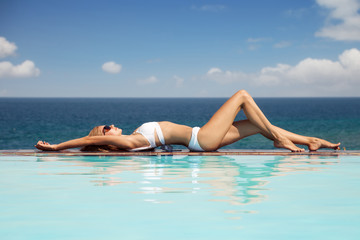Young beautiful woman sunbathing. Nice sea view from swimming po