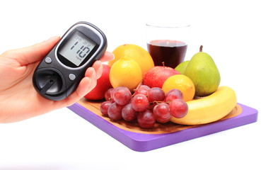 Hand of woman with glucometer and fresh fruits