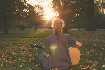Woman playing guitar at sunset in the park