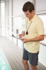 Swimming coach writing on clipboard