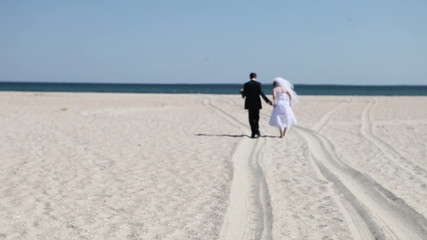 Bride with the groom walk along the sand to the sea