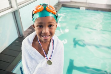 Cute little boy wrapped in towel with medal poolside