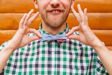 Fashion nerd correcting his bowtie