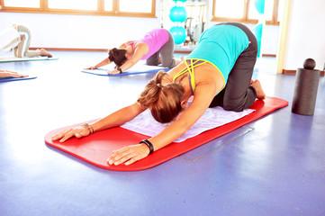Frauen machen Yoga im Fitnesscenter