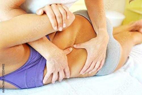Osteopath behandelt den Rücken einer Patientin - 72354462