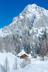 Winter rock with fresh fallen snow on top and house.