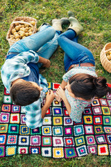Couple resting on a blanket on the grass in autumn