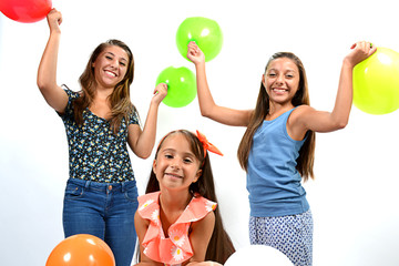 Smiling girls posing with colorful balloons