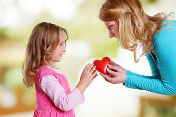 Frau schenkt Kind rotes Herz