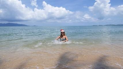 Beautiful Woman in Christmas Santa Hat and Bikini on Beach. Slow